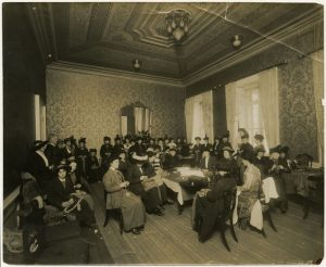 Photo Credit: The Rooms Provincial Archives: A 51-112; A work committee in the Ball Room of Government House. Note that some of the women are sewing by hand and machine; others are knitting.